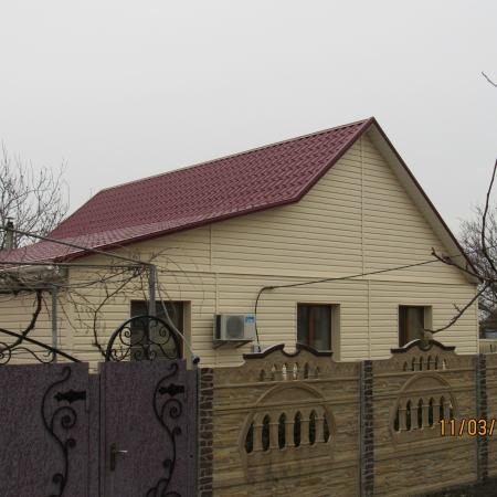 Вид дома из-за забора